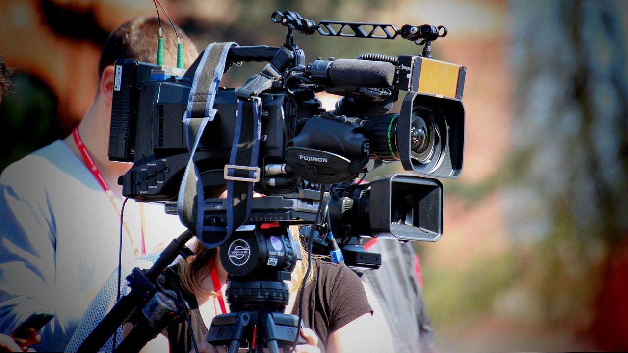 Three people standing behind TV camera