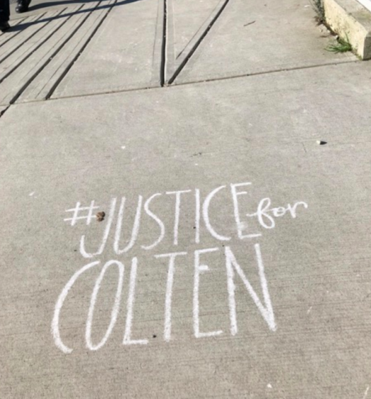 #JUSTICEforCOLTEN written in chalk on sidewalk.