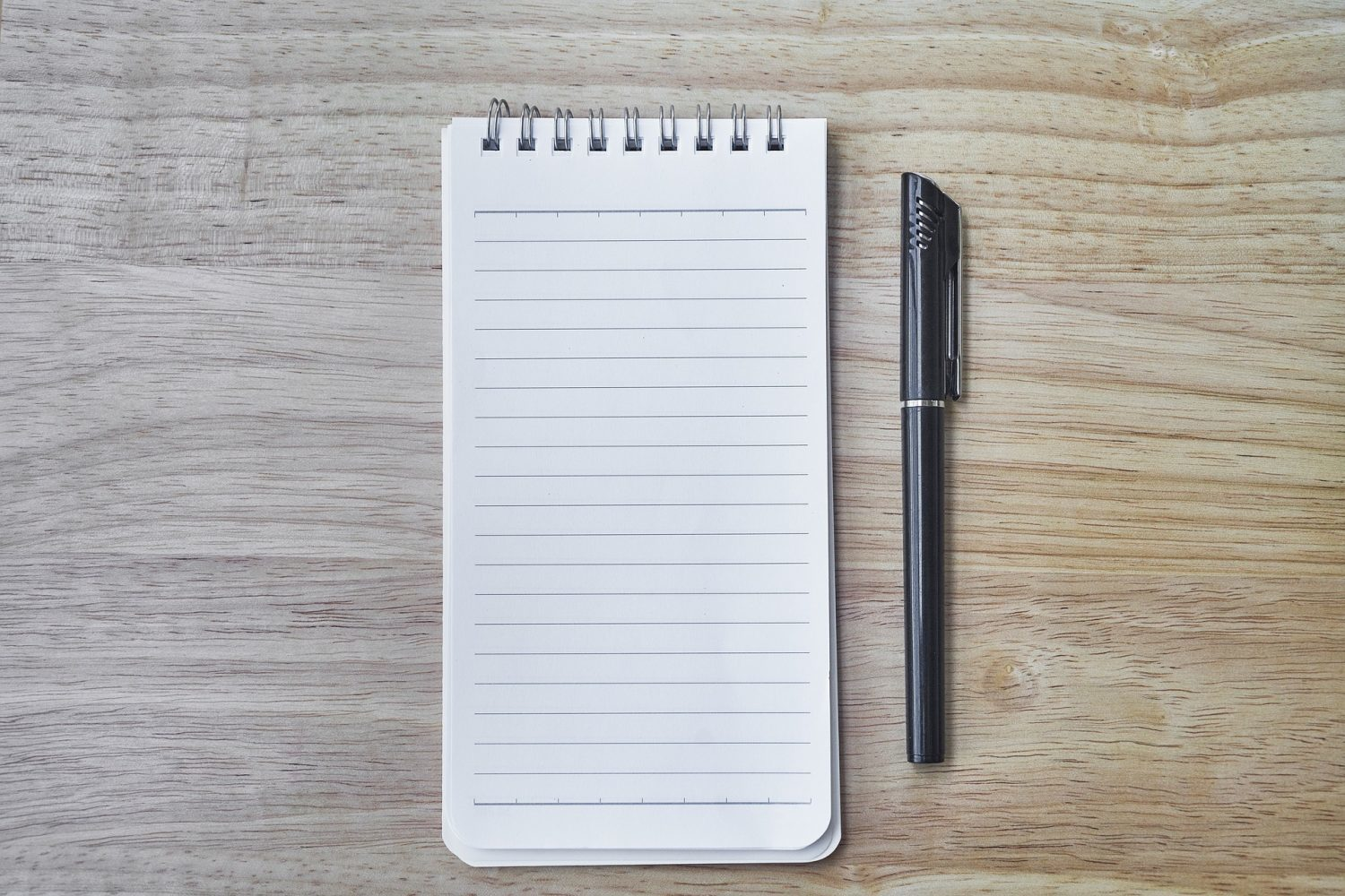Lined notepad and pen on wood table