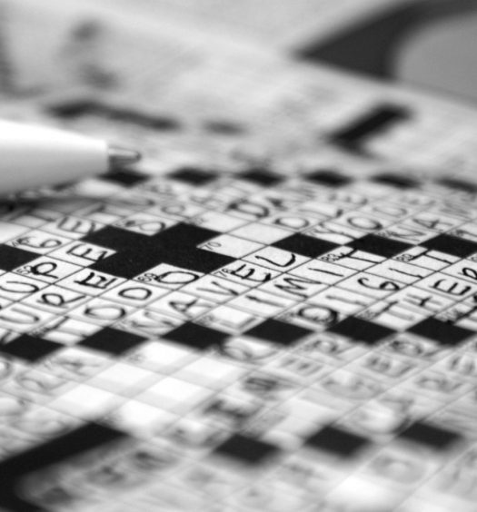 Close up of filled out crossword puzzle and tip of pen, in black and white