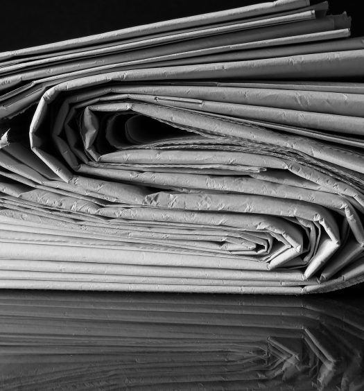 Stack of newspapers curved in s-shape, in black and white