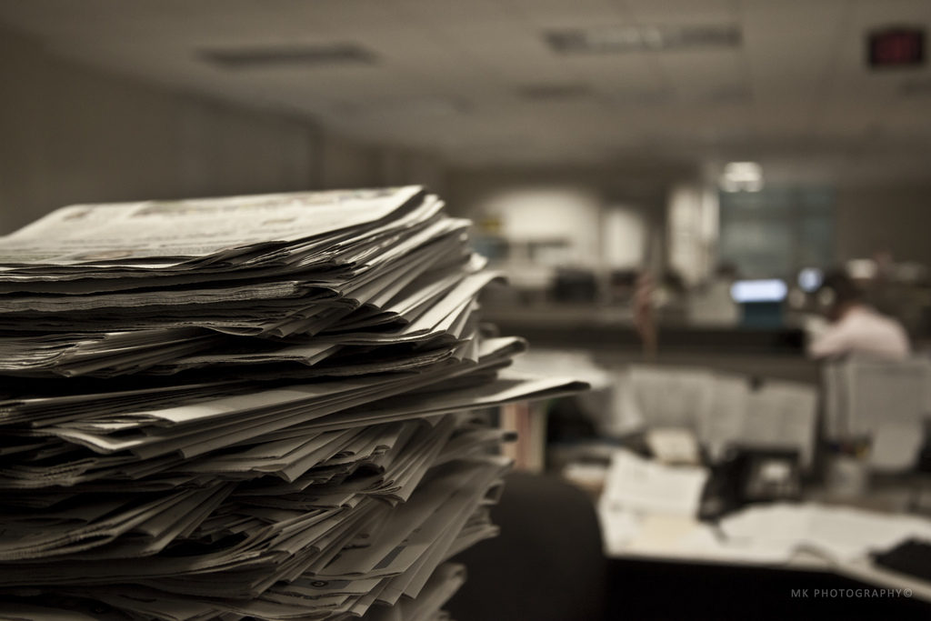 Stack of newspapers in foreground of office