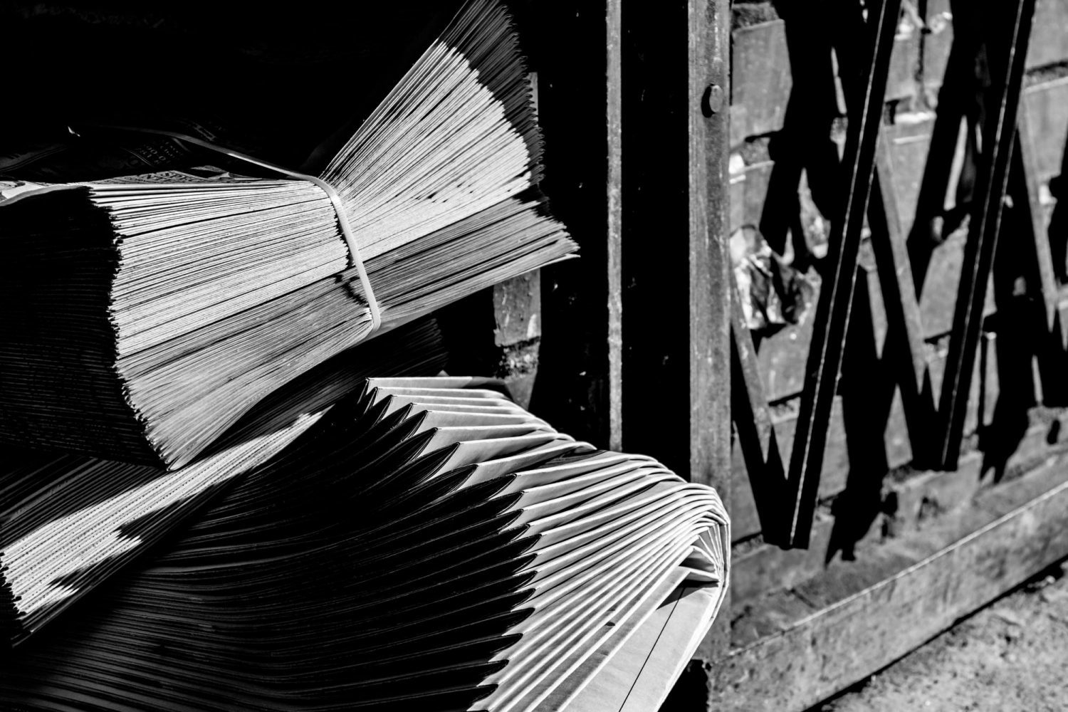 Two neatly bundles of neatly stacked newspapers on ground outside beside metal gate, in black and white