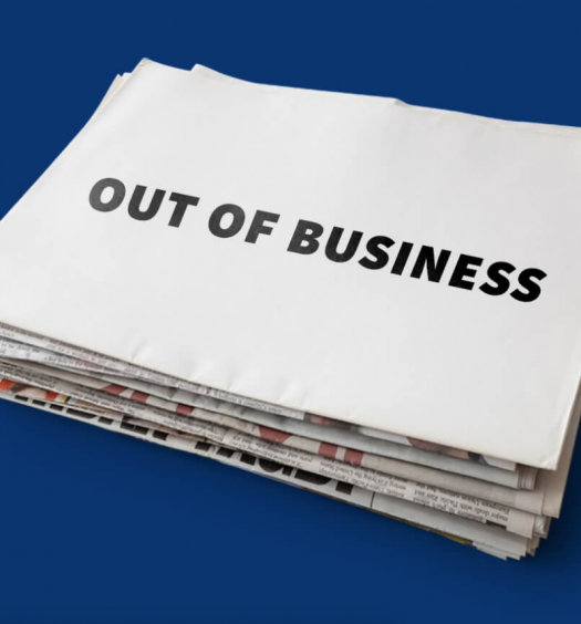 """Stack of newspapers with blank sheet on top that says """"Out of business"""" in all caps, black block letters, over dark blue background"""