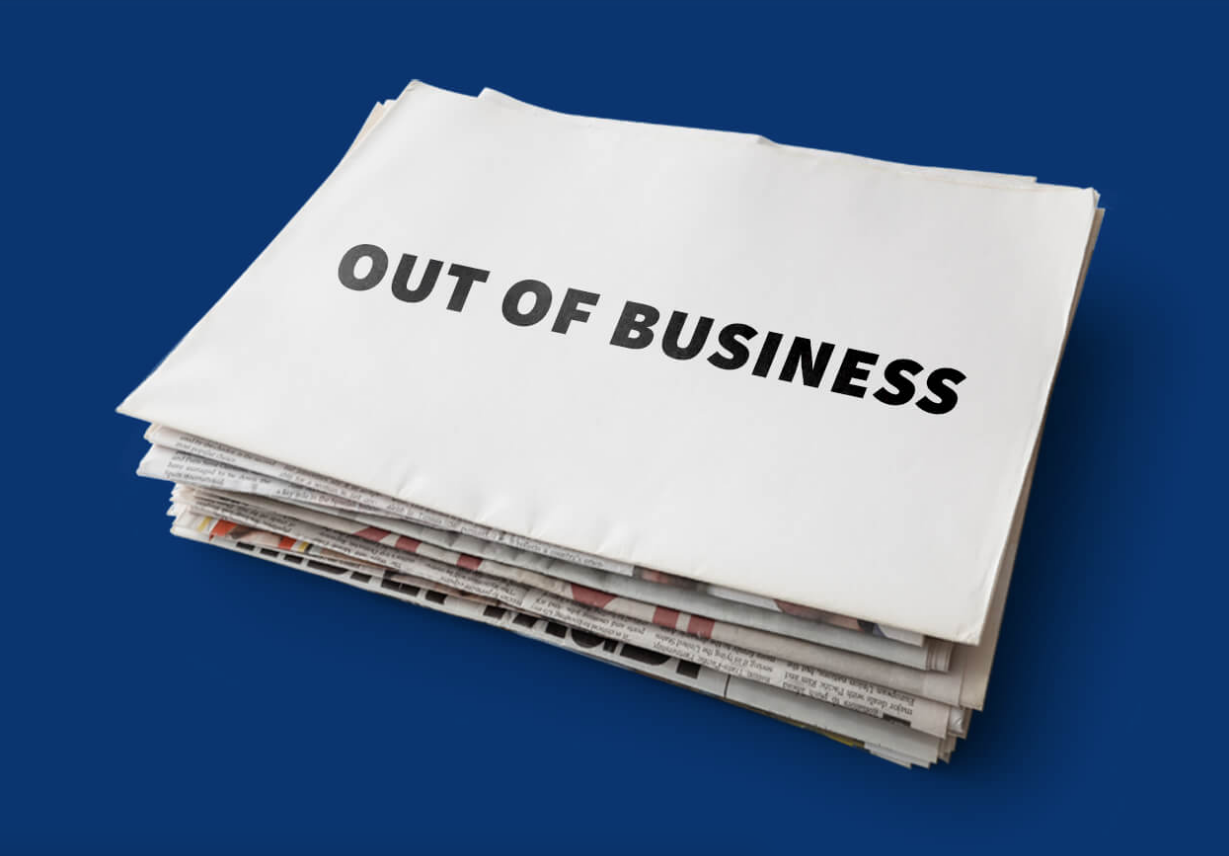 "Stack of newspapers with blank sheet on top that says ""Out of business"" in all caps, black block letters, over dark blue background"