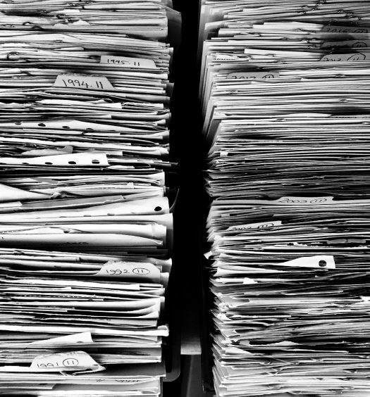 Two stacks of documents in file folders in black and white