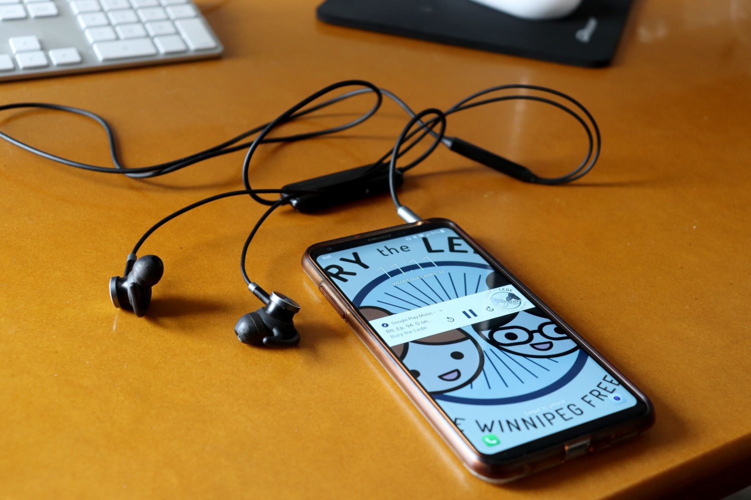 Smartphone with Bury the Lede open and earbud headphones on a computer desk