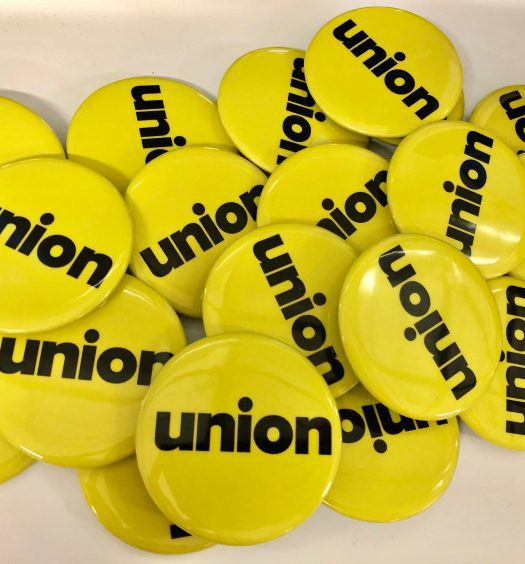 """Pile of yellow pin buttons with black text """"union"""""""