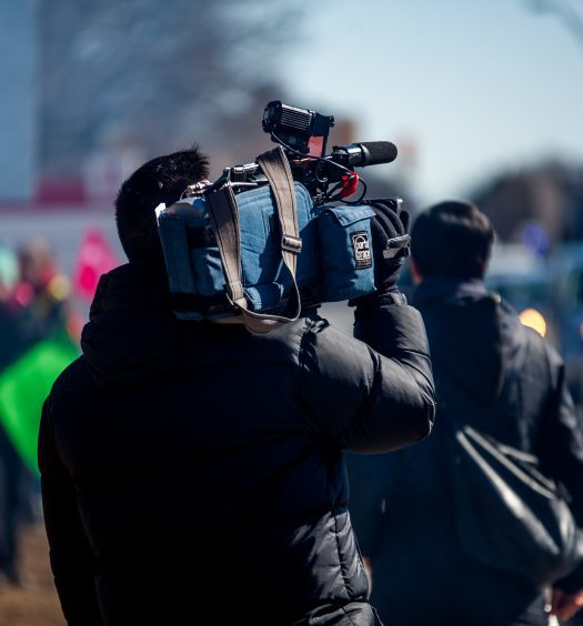 Back of person holding tv camera outside
