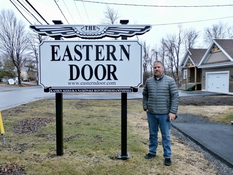 Steve Bonspiel stands in front of Eastern Door sign