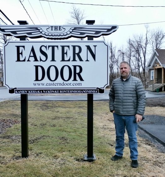 Steve Bonspiel stands in front of Eastern Door sign