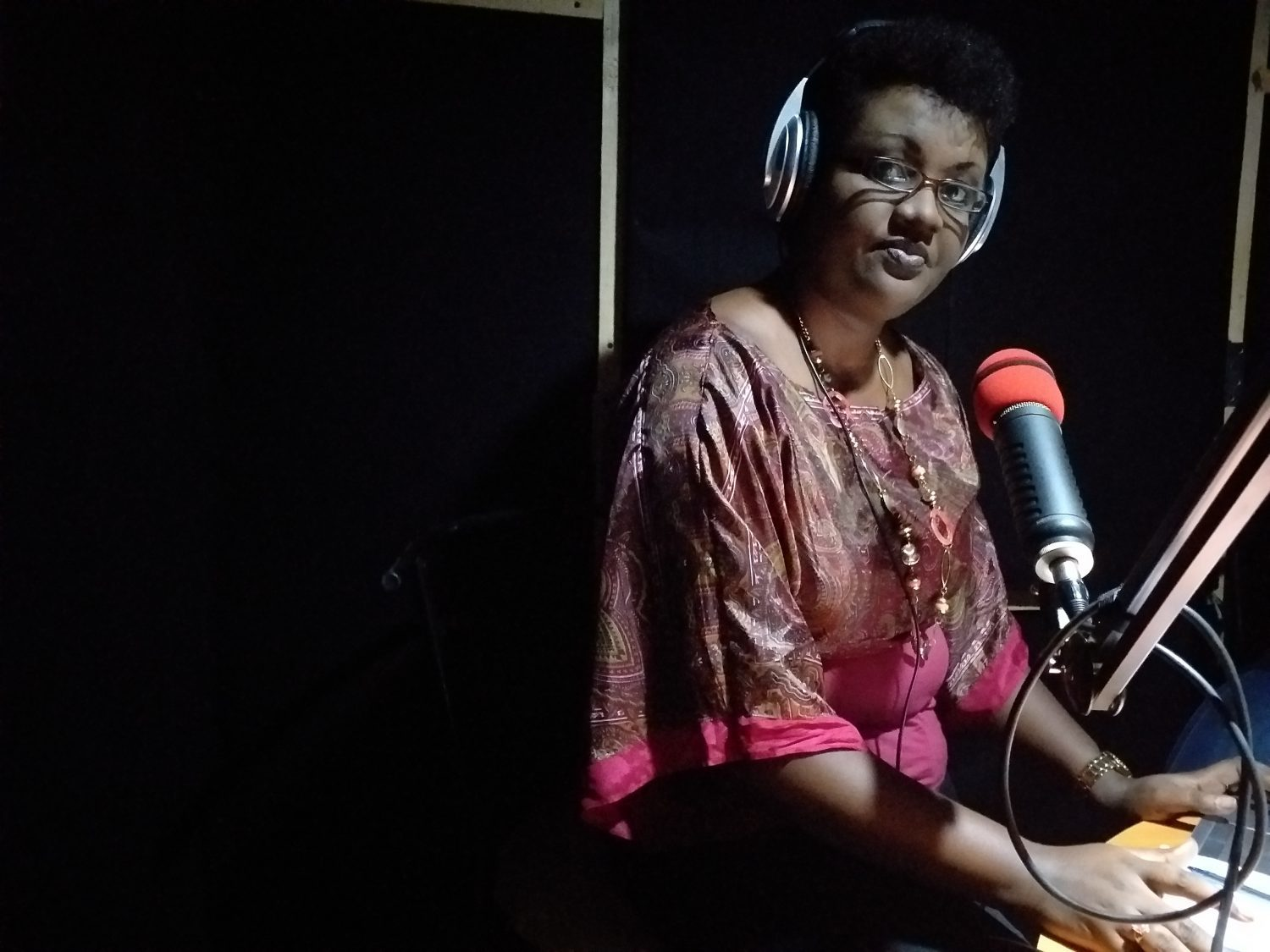 Reporter Josine Kaze records a news broadcast in the Inzamba studio, which was built in the converted living room of a private home