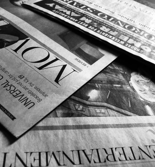 Toronto Star newspaper sections laid out overlapped, in black and white