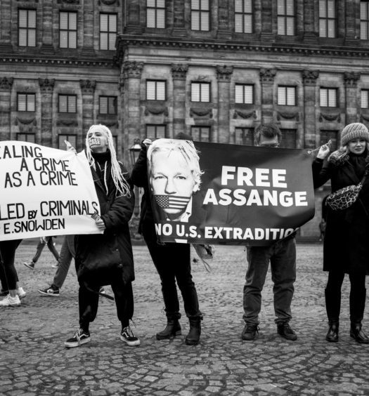 """A group of people outside holding signs supporting Julian Assange, including one that says """"Free Assange, no U.S. extradition"""""""
