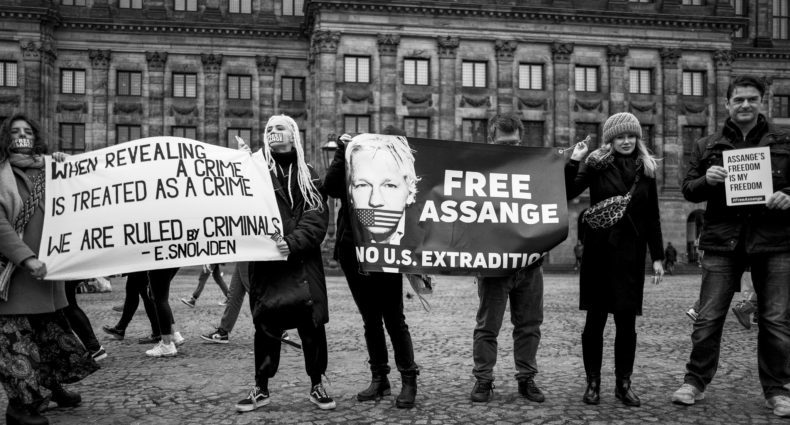 "A group of people outside holding signs supporting Julian Assange, including one that says ""Free Assange, no U.S. extradition"""