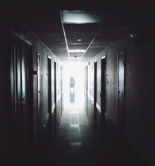 Dark hallway with silhoette or person standing at the end
