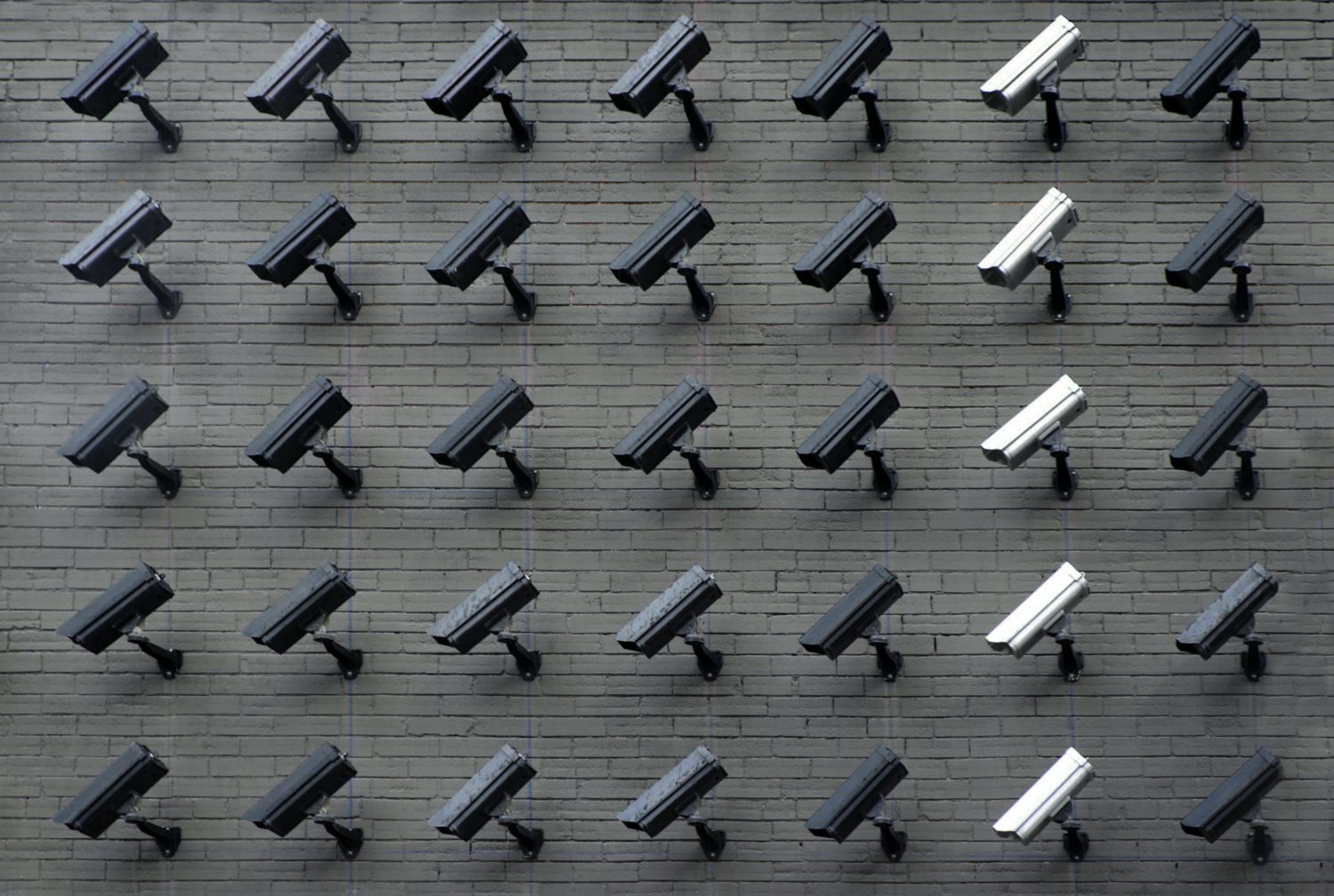 A brick wall of black and white surveillance cameras pointing down.
