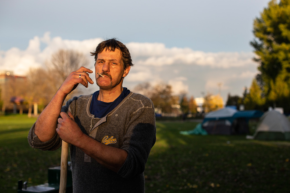 Eric Buurman takes a break from raking leaves near his tent at the same encampment.