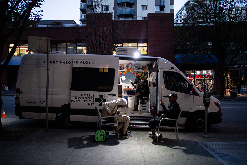 A harm-reduction worker sits with two other people who agreed to be photographed at the mobile overdose prevention unit in Yaletown at the location of a newly-approved permanent indoor OPS.