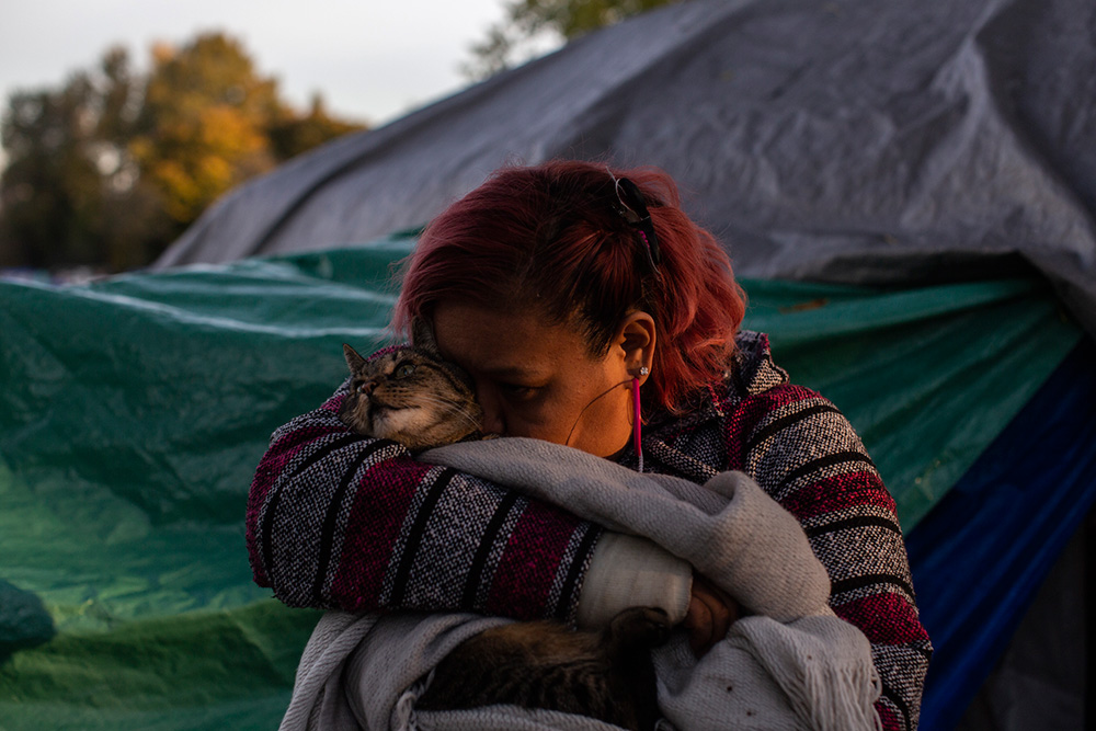 Roxanne Smythe snuggles her cat Chimo outside her tent at the Strathcona Park homeless camp.