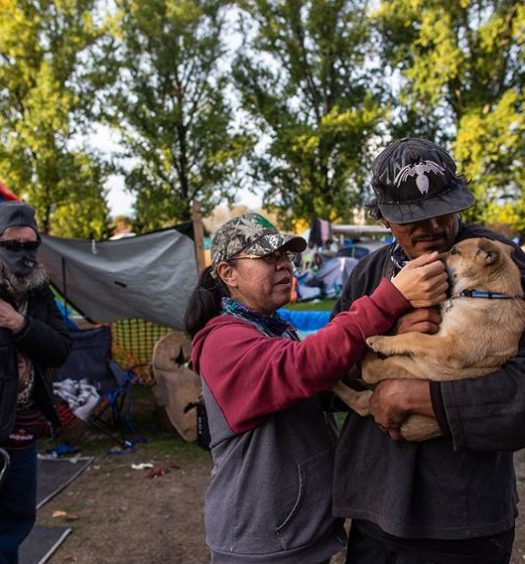 William Tomorowski and his partner Honey Turner play with their puppy Kalypso in the yard of their campsite at the Strathcona Park homeless encampment.