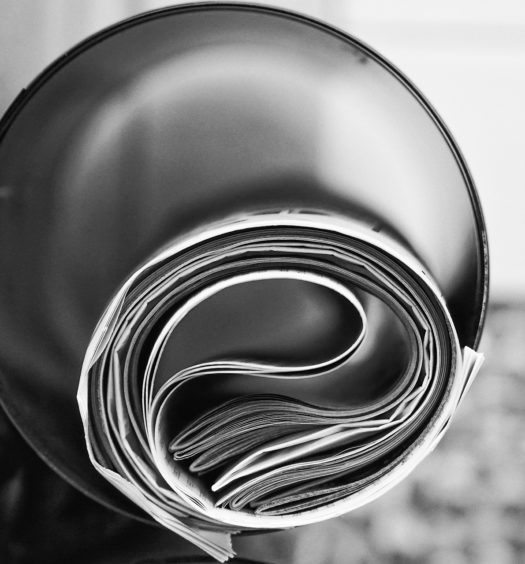 Black and white image of newspaper rolled up inside of tube