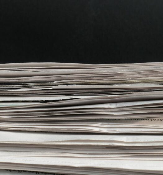 Stack of paper in front of black background.