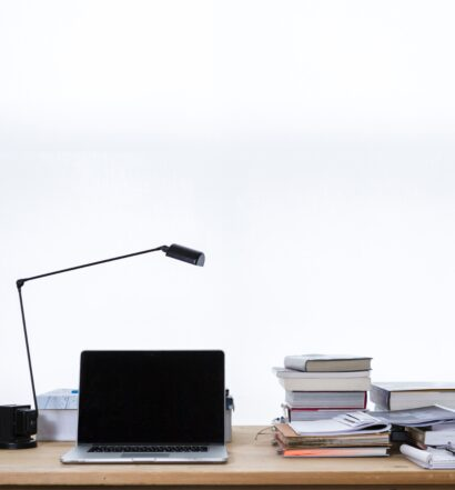 Laptop on wood desk with a lamp, stacks of books and folders in front of a white wall.