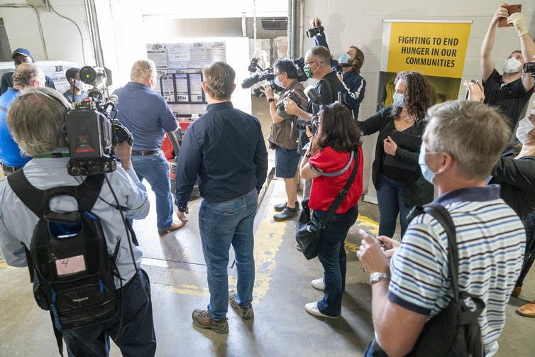 Journalists at a media scrum reporting on the opening of a new Daily Bread Food Bank in Toronto in May 2020.