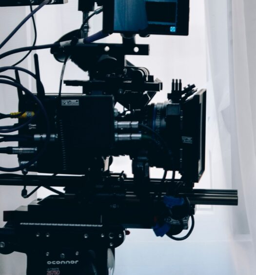 TV camera pointing right in front of a white curtain