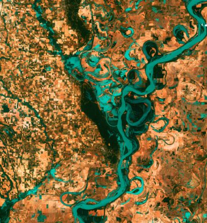 "Small, blocky shapes of towns, fields, and pastures surround the graceful swirls and whorls of the Mississippi River. Countless oxbow lakes and cutoffs accompany the meandering river south of Memphis, Tennessee, on the border between Arkansas and Mississippi, USA. The ""mighty Mississippi"" is the largest river system in North America."