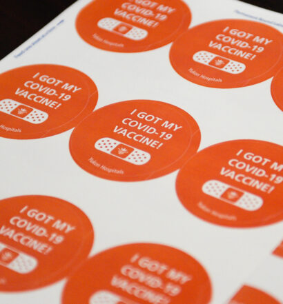 """A sheet of 9 orange COVID-19 vaccination stickers on white paper, that say """"I GOT MY COVID-19 VACCINE!"""" with a drawing of a bandaid underneath. Bottom reads """"Yukon Hospitals"""""""