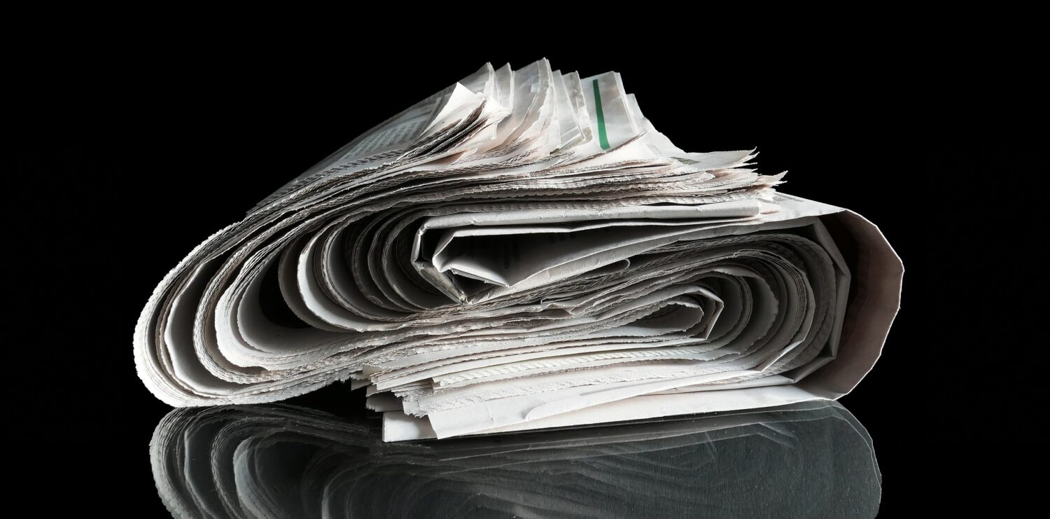 Newspaper rolled in S-curve on black background