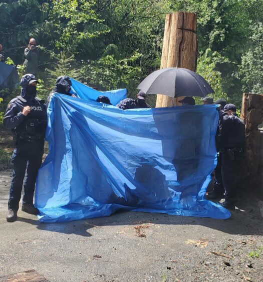RCMP using tarps to obstruct media access as an arrest takes place last week.