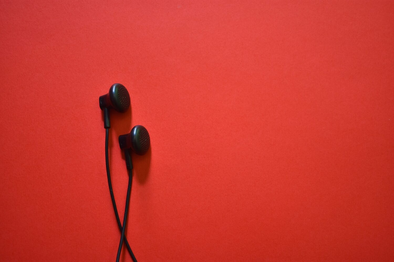 Black earbud headphones on red background