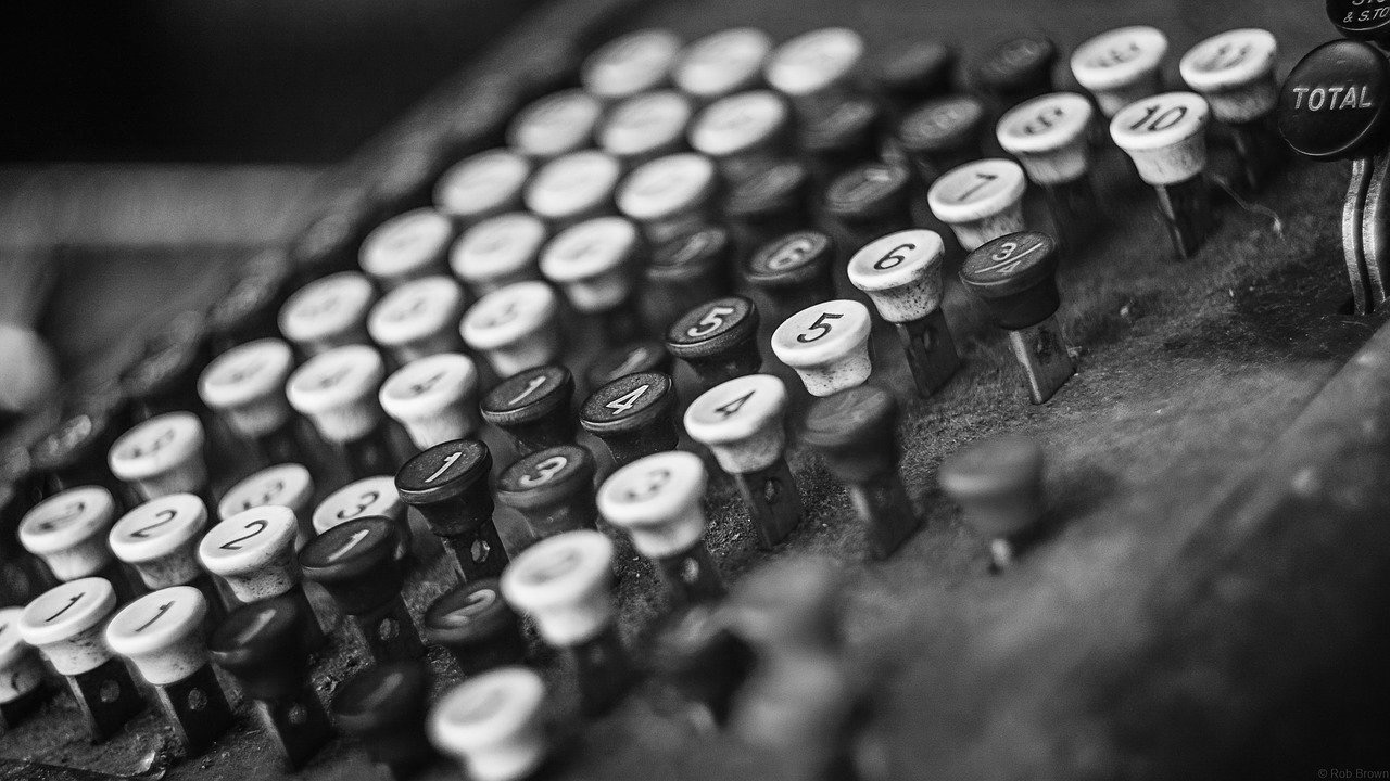 Close-up of vintage cash register in black and white.