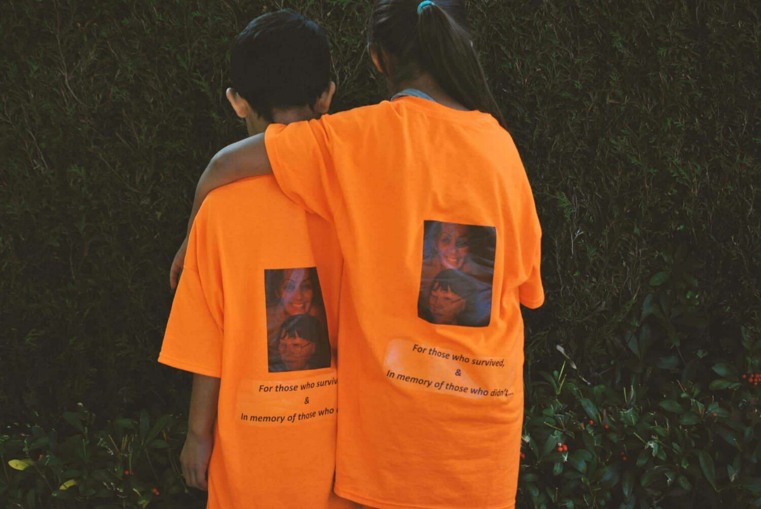 """Two children, one with arm around the other facing away, wearing orange t-shirts that read """"For those who survived & in memory of those who didn't"""""""