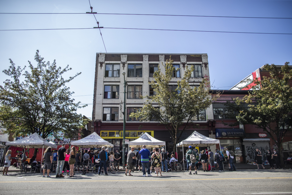People gather on East Hastings Street to remember Thomus Donaghy, an overdose prevention worker who was stabbed to death on July 27, 2020, while he was on duty.