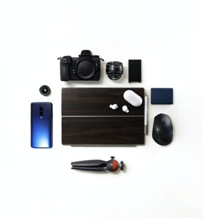 Smart phone, laptop, camera, lens, computer mouse and earbuds on white background