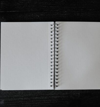Blank spiral-bound notebook open on black background